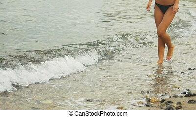 Close up of female walking on the desert beach.
