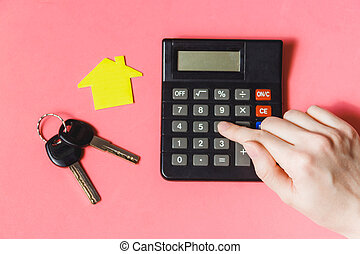 Close-up Of Female's Hand Using Calculator With Paper House Model On Desk with Diagram.