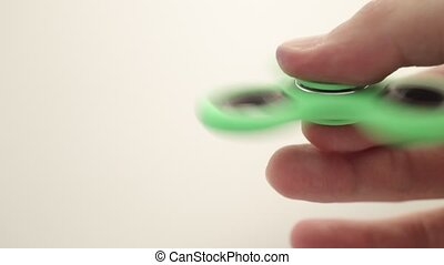 Close up of fidget spinner rotating on male hand over white...