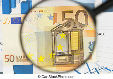 Close-up of fifty euros through a magnifying glass. Business background. Money research concept.