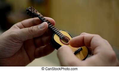 Close - up of fingers playing a small toy guitar