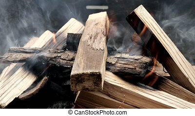 Close up of fire on chargrill. Dry sticks smoulder. Concept of cooking on grill.
