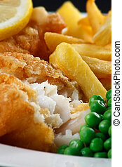 Close up of fish and chips with peas and a slice of lemon. A...