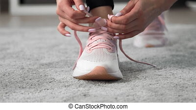 Close up of fitness girl tying laces on sport sneakers on ...
