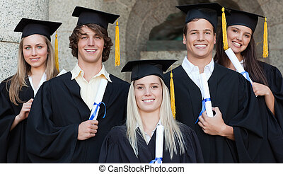 Close-up of five happy graduates posing