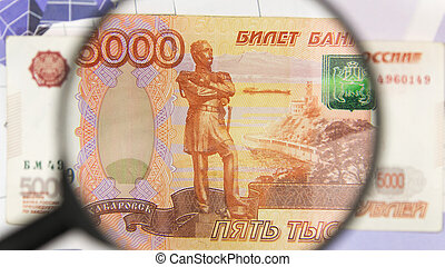 Close-up of five thousand rubles through a magnifying glass. Business background. Money research concept.