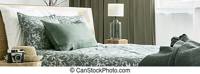 Close-up of floral bedsheets and green cushion on bed next to wooden stool with a straw hat and vintage camera in bedroom for a traveler