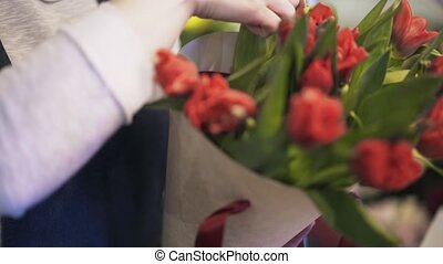 Close up of florist arranging red flowers