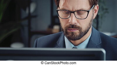 Close up of focused man in eyewear working on computer - ...