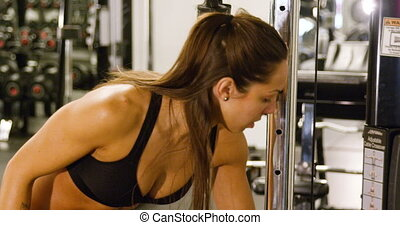 Close-up of focused woman training triceps muscles pulling cable machine in gym