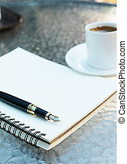 Close up of Fountain pen with notebook on coffee table