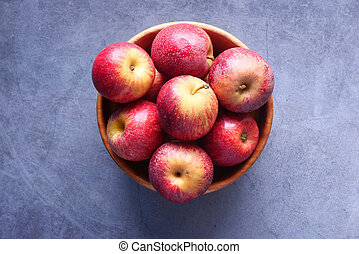 Close up of fresh apple in a bowl on wooden table