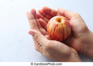 Close up of fresh apple on women's hand