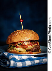 Close Up of Fresh Burger on Dark Rustic Wooden Surface with Blue Background
