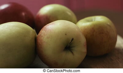 Close up of fresh delicious red and green apples on a table, wooden background.