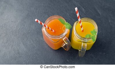close up of fresh juices in mason jar glasses