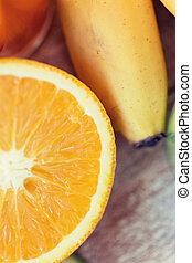close up of fresh juicy orange and banana on table