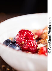 Close up of fresh red raspberry with ingredients for healthy organic dieting breakfast in a white bowl on a wooden table.