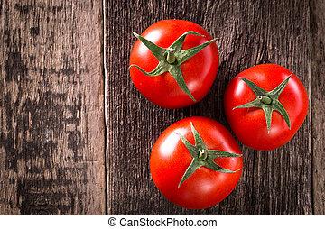 Close-up of fresh, ripe tomatoes on wood background