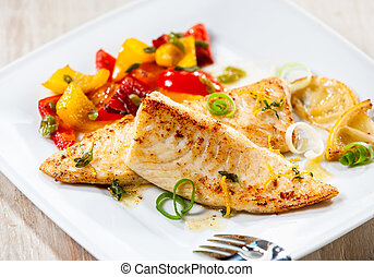 Close up of fresh tilapia fish fillet wit bbq grilled vegetables on white dish or plate on wooden background