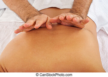 Close up of male back friction massage done with back of the hand