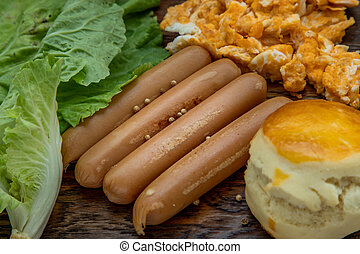 Close-up of fried sausages and scrambled eggs, scones with vegetable on wooden background.