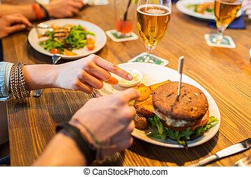 close up of friends hands sharing burger at bar