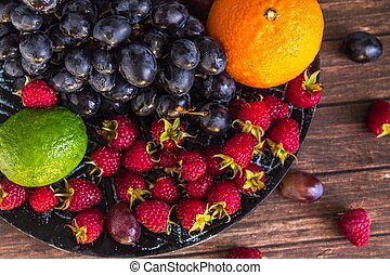 close-up of fruit salad with raspberries, grape, lime on a clay plate on a rustic wooden table, view from above, macro