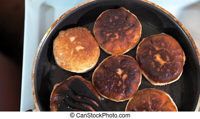 Close-up of frying pan with butter fry meat pies.