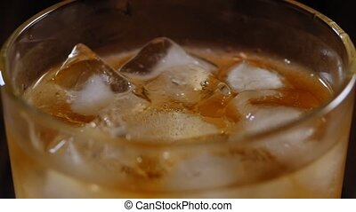Close-up of full glass of whiskey with ice slowly rotates on a black background.