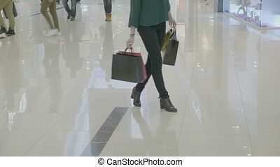 Close up of funny happy woman in heels carrying shopping bags walking in a fashion way spinning and dancing in the mall