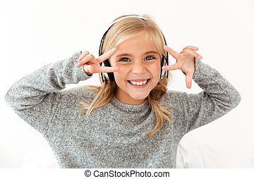 Close-up of funny little girl in hedphones showing peace gesture with two hands, lookin at camera
