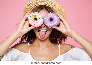 Close-up of funny pretty girl in straw hat looking through two sprinkled donuts