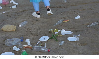 Close-up of garbage and waste on the sand, volunteers clean up garbage.