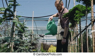 Close-up of garden tools. Gardener going to the greenhouse, watering plants from a green funnel. Garden center decorative plants and flowers.
