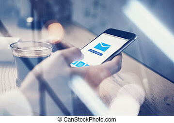 Close up of generic design smart phone holding in female hands for texting message. Sending message icon on screen. Cup coffee the table. Horizontal