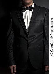 Close-up of gentleman wearing black tie straightens his bowtie on black