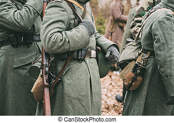 German military ammunition of a German soldier at World War II. Warm autumn clothes, soldier's overcoat, gloves, helmet, pouch, sapper shovel, flask, rifle, storage box case for gasmask.