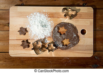 close up of ginger dough, molds and flour on board