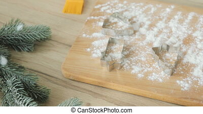 Close-up of gingerbread dough with flour and cookie cutter on table. making gingerbread christmas cookies with all the ingredients and utensils - top view