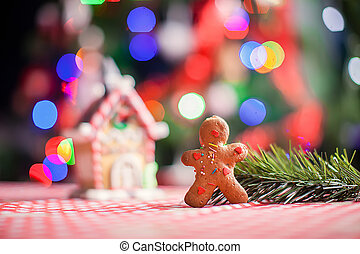 Close-up of gingerbread man background candy ginger house and Christmas tree lights