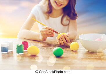 close up of girl coloring easter eggs