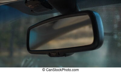 girl corrects car rearview mirror - close up of girl...