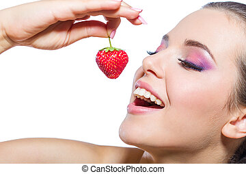 Close up of girl eating strawberry with closed eyes