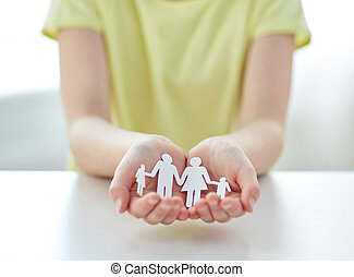 close up of girl hands with paper family cutout
