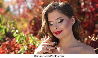 Close-up of girl in a beautiful evening dress walking in the autumn golden park.