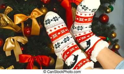 girl in a funny sock with ornament near the Christmas tree