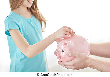 close up of girl putting coin into piggy bank