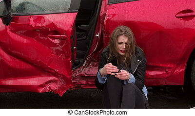 Close-up of girl sitting on the ground near a broken car, she was in an accident