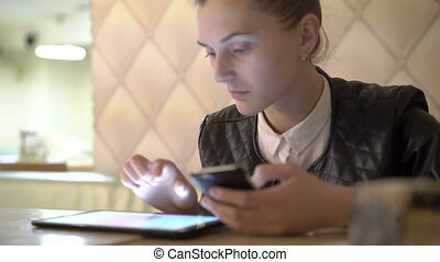 Close up of girl using tablet and phone in cafe. 4K